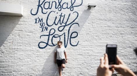 ミズーリ州カンザスシティにある壁画の前でポーズを取ります