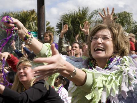 ラファイエットのマルディグラパレードでビーズをキャッチして盛り上がる人々